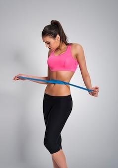 Focus woman measuring her waist after workout