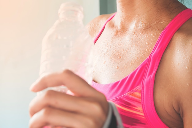 Focus on woman's body with sweat on tanning skin