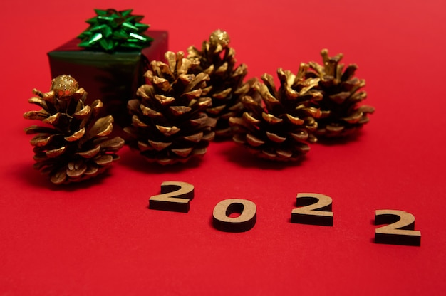 Focus on wooden numbers, symbolizing the year 2022 on the red background with christmas in glitter wrapping paper with green bow gift and pine cones with golden ornament,with copy space for ad