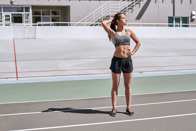 Focus on your goals attractive athlete on the stadium track woman summer fitness workout jogging