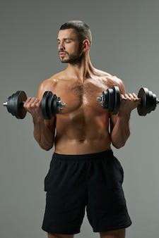 Сосредоточенный очаровательный кавказский мужчина в спортивной одежде, поднимающий тяжести, изолированные на сером фоне