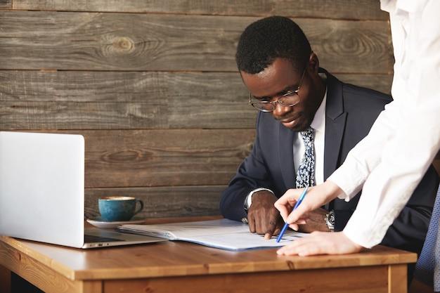 Сосредоточенный афро-американский бизнесмен проверяет документы со своим личным помощником в белой рубашке