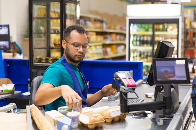 Сосредоточенный афроамериканец кассир, сканирующий товары при оформлении заказа