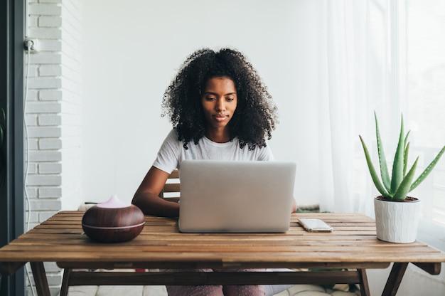 Ориентированные афроамериканские женщины с вьющимися волосами, сидя за столом