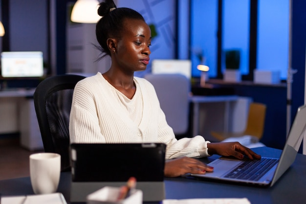 Focused african entrepreneur writing on laptop late at night to finish deadline