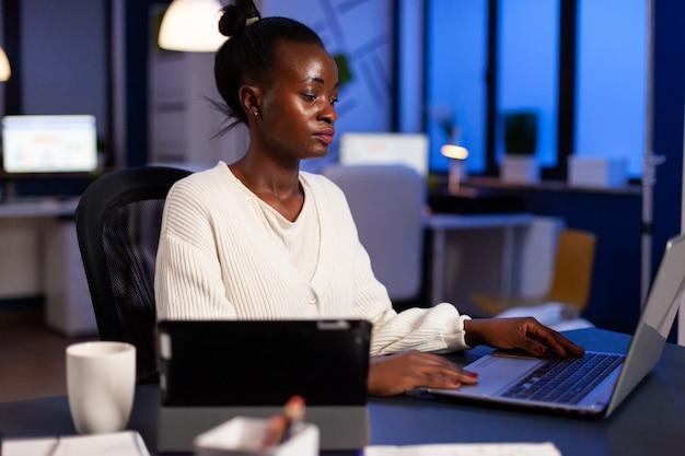 마감일을 끝내기 위해 늦은 밤 노트북에 글을 쓰는 아프리카 기업가