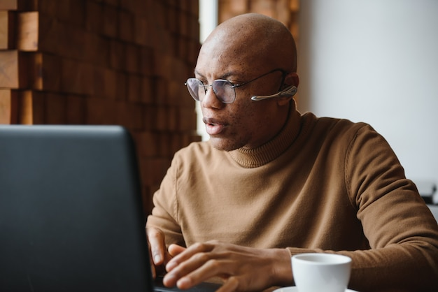 Focused african man wearing headphones watching webinar training making notes
