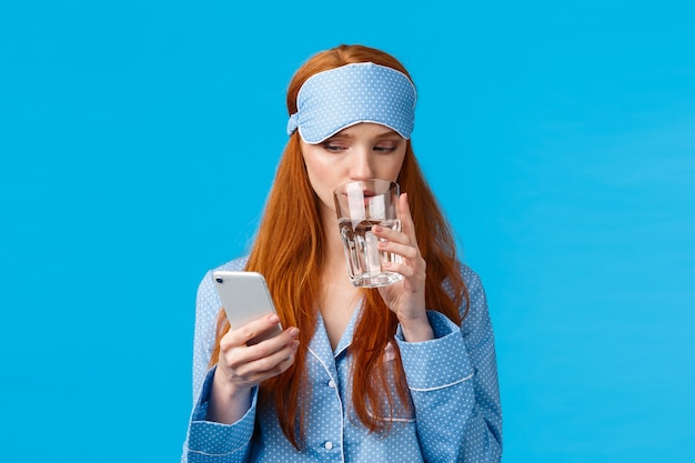 グラマー睡眠マスクと集中して電話中毒の赤毛白人女性