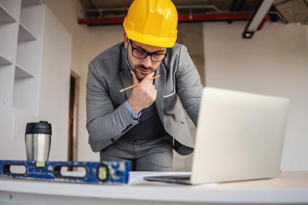 청사진을보고 건설 현장에서 책상에 기대어 생각하는 집중된 건축가.