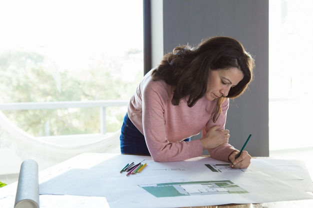 Focused architect working on building plan