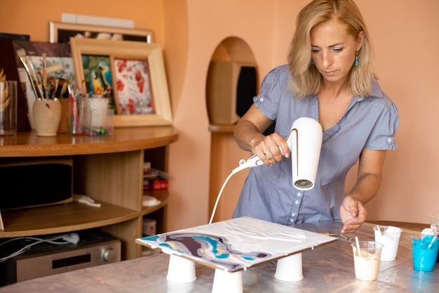 Сосредоточенный художник использует краски и фен для создания современной интерьерной живописи в своей мастерской. увлечения . живопись в интерьере. домашний досуг. творчество и творчество. мастер-класс по живописи.