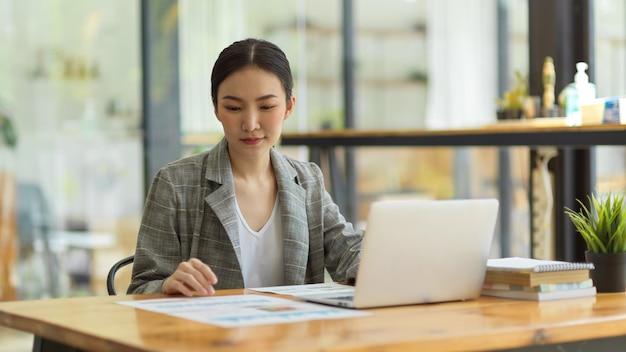 机に座って、プロジェクトに取り組んで、ラップトップで入力し、財務報告に集中し、カフェのコワーキングスペースで働くことに焦点を当てたアジアの女性サラリーマン