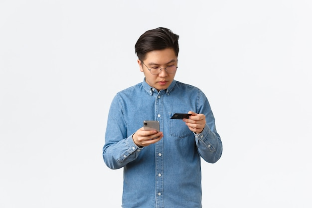Focused asian guy in glasses typing credit card number to make online purchase, using mobile phone and bank account to buy something in internet store, standing white background.