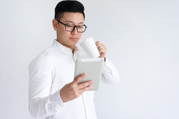 Focused asian man using tablet and drinking coffee