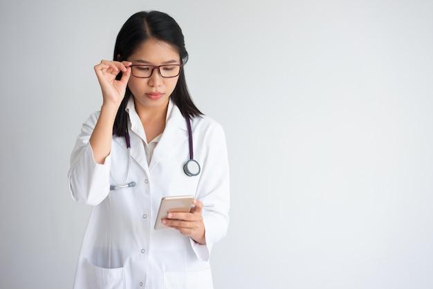 Focused asian medical student using phone
