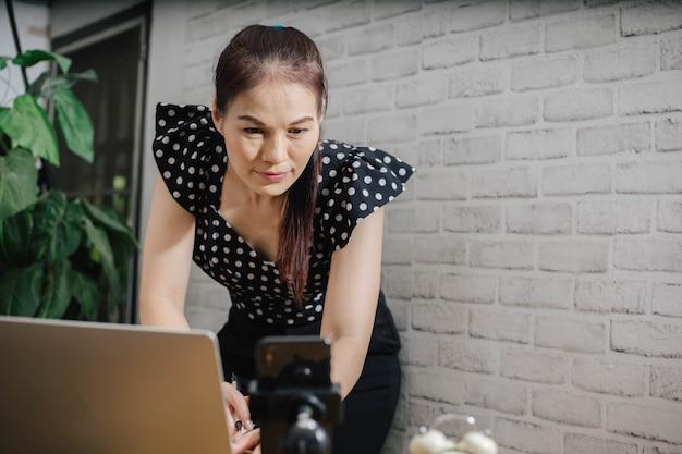 自宅でノートパソコンを使用し、画面を見たり、チャットしたり、メールを読んだり書いたりすることに焦点を当てたアジアの女性。