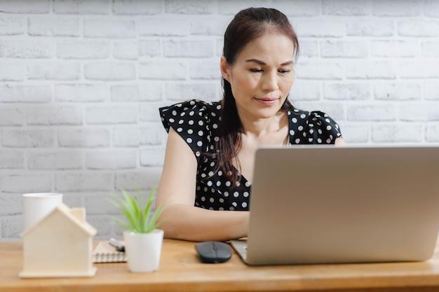 Сосредоточенная азиатская женщина, использующая ноутбук дома, смотрящая на экран, болтающая, читающая или пишущая электронную почту.