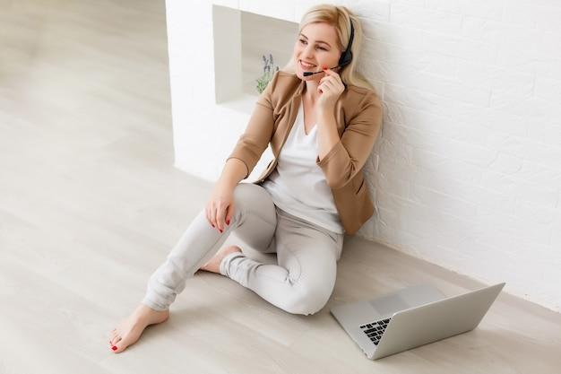 ヘッドフォンで集中力のある気配りのある女性は、ラップトップに座って、画面を見て、メモを取り、インターネットで外国語を学び、オンライン学習コース、ウェブでの自己教育、ビデオでクライアントに相談します
