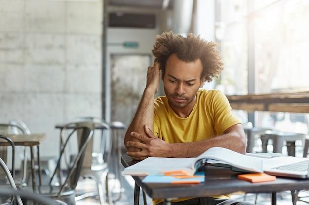 Сосредоточенный привлекательный афроамериканский студент университета учится в современном кафе, изучает новую информацию из учебника во время подготовки к экономике.