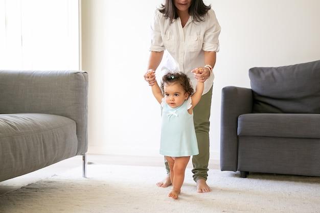 ママの手を握り、家で歩こうとしている淡いブルーのドレスに焦点を当てた女の赤ちゃん。全長。親子関係の概念
