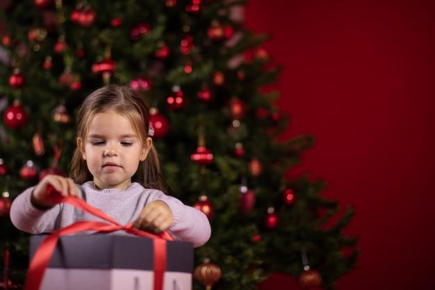 クリスマスツリーの横に焦点を当てた女の赤ちゃんオープニングギフト