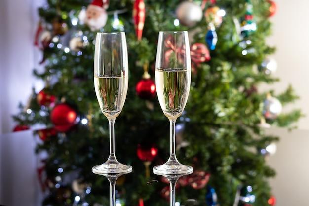 Фокусный фон с двумя шампанскими стеклами на столе из темного стекла перед рождественским деревом