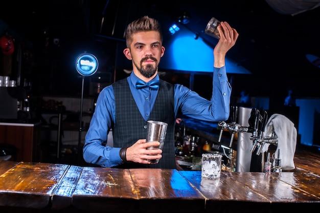 Сосредоточенный бармен украшает красочную смесь, стоя возле барной стойки в баре