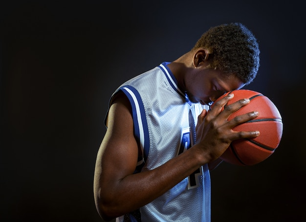 Focused basketball player poses with ball in studio, black background. professional male baller in sportswear playing sport game, tall sportsman