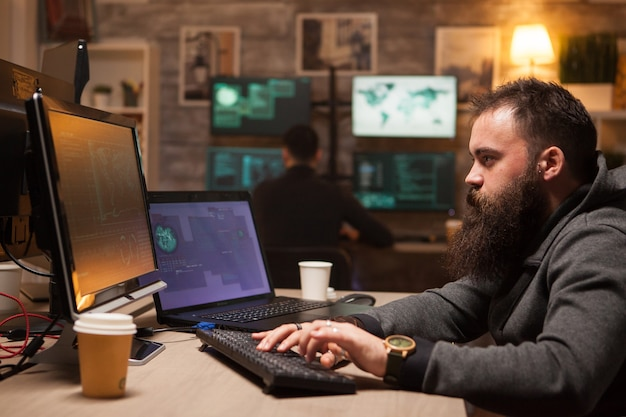 Сосредоточенный бородатый хакер после того, как выпил много кофе, не заснул. молодой киберпреступник на заднем плане.