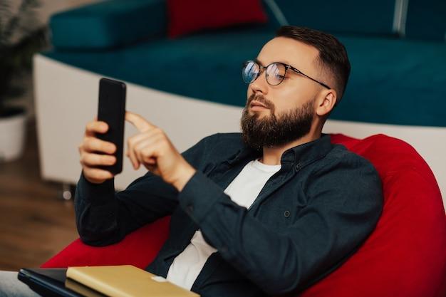 Сосредоточенный бородатый мужчина в синей рубашке и очках использует смартфон, сидя в красном кресле дома.