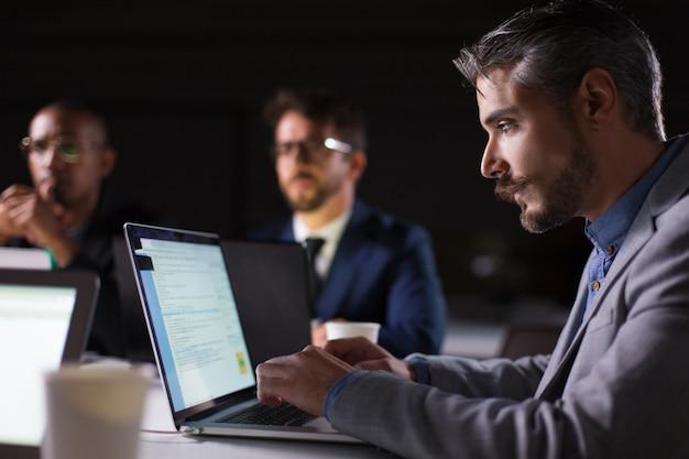 Focused bearded office employee looking at laptop