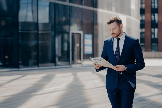 Focused bearded young businessman in formal outfit walking alone with newspaper in hands, reading latest news on his way to workplace with office buildings in background