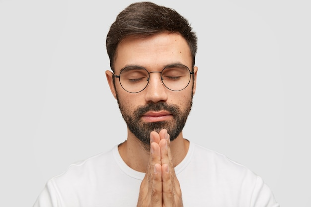 Focused bearded young man model keeps palms in praying gesture, believes in good fortuney.