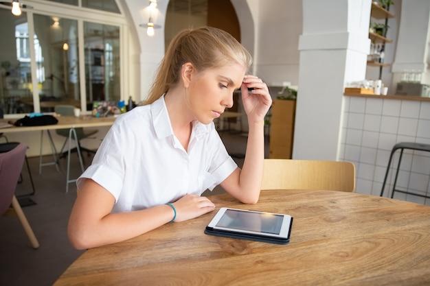 コワーキングスペースのテーブルに座って、タブレットを使用して、画面上のテキストを読んで、白いシャツを着て焦点を当てた美しいブロンドの女性