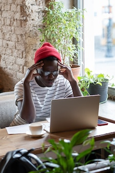 Focused black freelancer man watching educational webinar on laptop, remotely online work in cafe