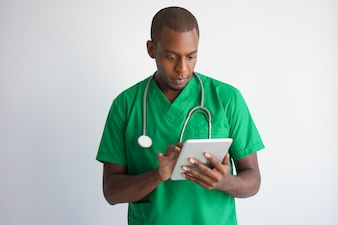 Focused black male doctor using tablet computer.