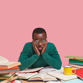 Focused black male wonk gazes at opened books, touches cheeks, looks surprisingly at topic for learning, wears green jumper