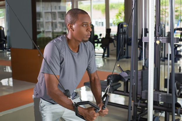 Focused black man exercising pecs on gym equipment