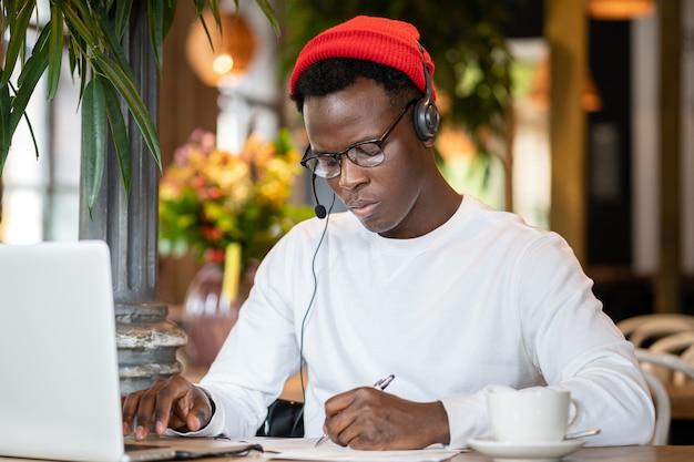 Focused black man in headphones watching educational webinar on laptop remotely online work in cafe