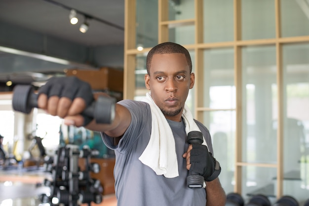 Focused black man holding dumbbells and boxing