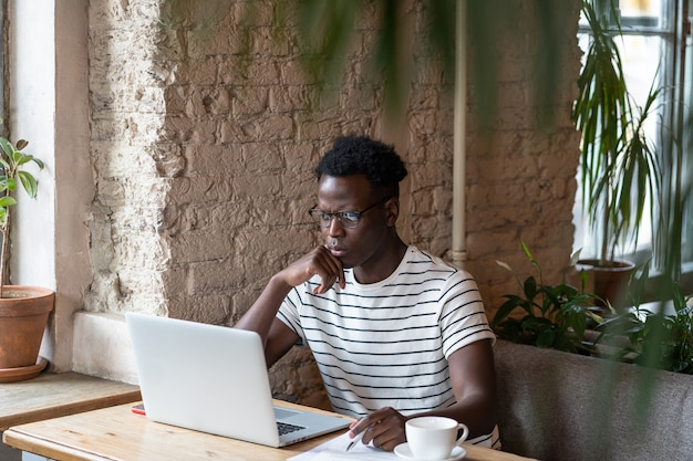 Сосредоточенный черный студент смотрит образовательный веб-семинар на ноутбуке
