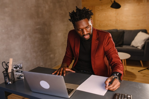 A focused black man in a suit is working on a laptop. remote work from home.