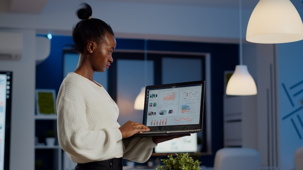 Focused black manager woman checking business report standing in start up office late at night holding laptop. busy african employee analysing financial statistics overworking writing, searching.