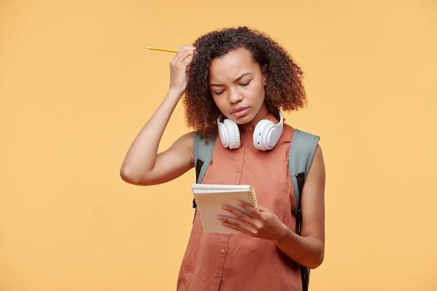 タスクの解決策を考えている間首の周りにワイヤレスヘッドフォンで頭を掻く焦点を当てた黒人学生の女の子