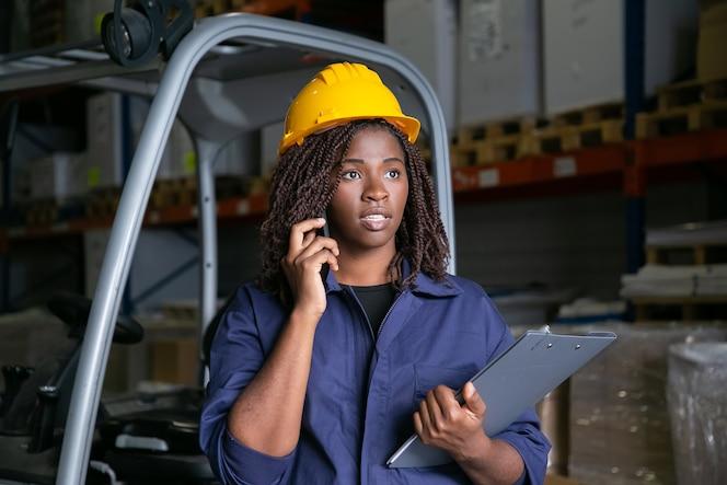 フォークリフトの近くに立って独房で話している黄色いヘルメットをかぶった黒人の倉庫作業員に焦点を合わせた。背景に商品が入った棚。ミディアムショット。労働またはコミュニケーションの概念