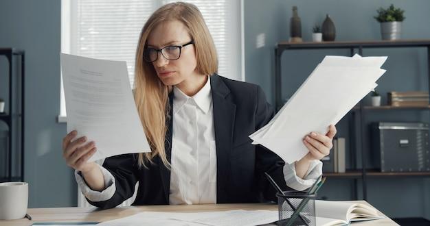 紙のレポートを読んで多くのドキュメントを保持しているオフィスのテーブルに座っている焦点を当てた金髪のビジネスレディ