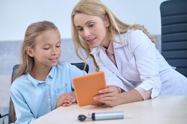 Focused blonde attractive middle-aged doctor demonstrating something at her tablet computer to a young girl