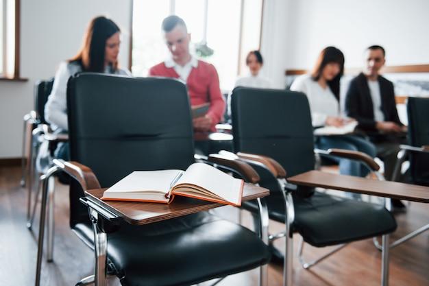 Incentrato sul libro. gruppo di persone alla conferenza di lavoro in aula moderna durante il giorno