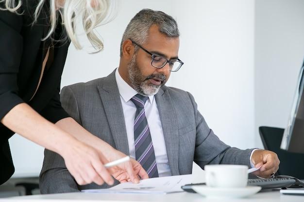 집중된 보스 분석 관리자 보고서, 직장에 앉아있는 동안 서류를 읽고 검토합니다. 비즈니스 커뮤니케이션 개념