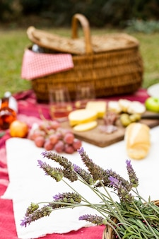 Focused bouquet of lavender next to picnic goodies